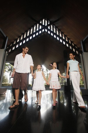 Family walking into resort while holding hands Stock Photo - 7362277