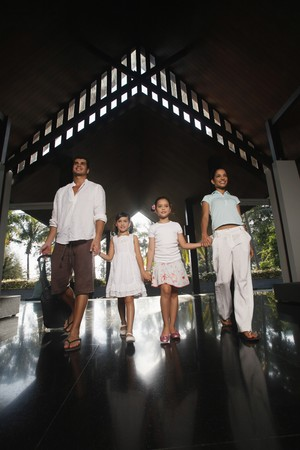 Family walking into resort while holding hands Stock Photo - 7362276
