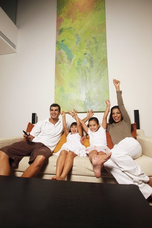 Family watching tv together, all cheering with arms raised photo