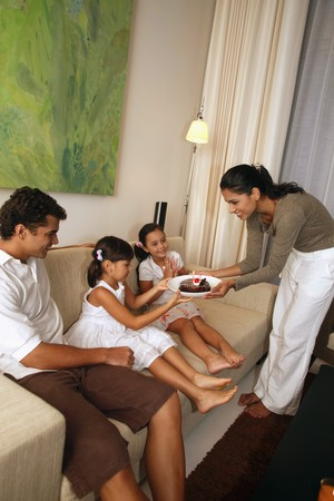 Woman surprising girl with chocolate cake, family sitting in the living room Stock Photo - 7362304