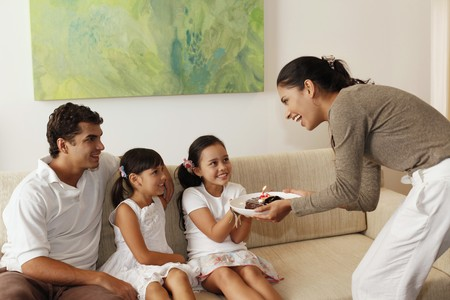Woman surprising girl with chocolate cake, family sitting in the living room