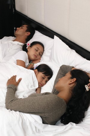 Family sleeping together on bed photo