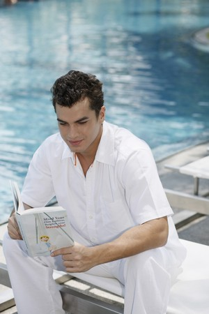 Man reading book by the pool side Stock Photo - 7361977