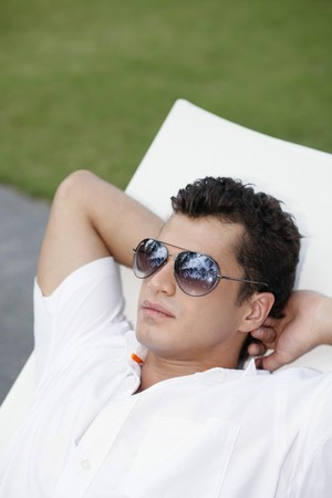Man with sunglasses relaxing on lounge chair photo
