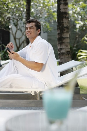 Man sitting on lounge chair text messaging on the mobile phone photo