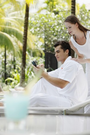 Man text messaging on the mobile phone, woman watching from behind Stock Photo - 7362006