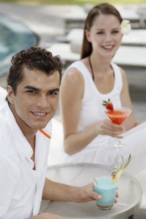 Man and woman on lounge chairs with their drinks Stock Photo - 7361818