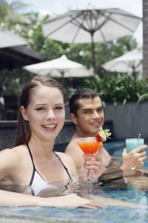 central european ethnicity: Hombre y mujer sentada en la piscina con su bebida