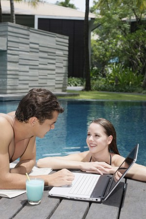 Woman in pool talking to man photo