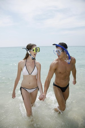 Man and woman with snorkeling gear on beach photo