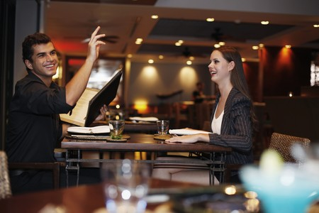 table of contents: Man holding menu and raising his hand, woman watching man Stock Photo