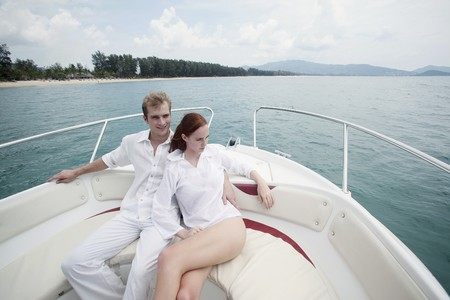 romance image: Man and woman resting on speedboat
