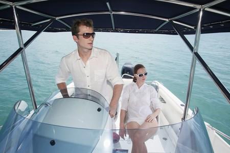 Man steering speedboat, woman sitting beside him photo