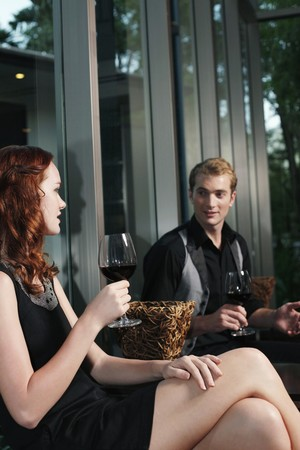 Man and woman holding glasses of red wine while chatting photo