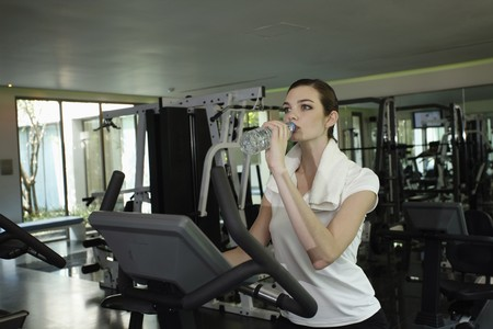 Woman drinking water while exercising in the gymnasium Stock Photo - 7446040