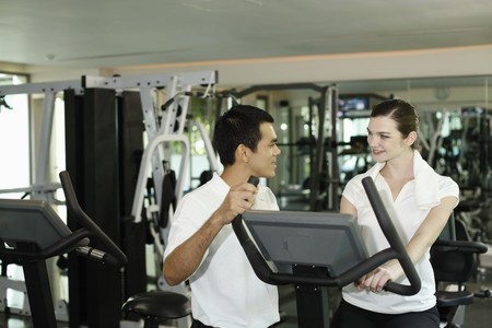 gymnasium: Personal trainer helping woman exercising in gymnasium