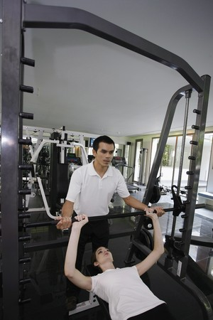 Personal trainer helping woman exercising in gymnasium Stock Photo - 7446734