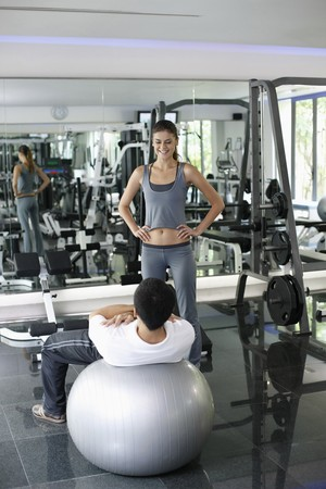 Personal trainer helping man exercising in gymnasium Stock Photo - 7446932