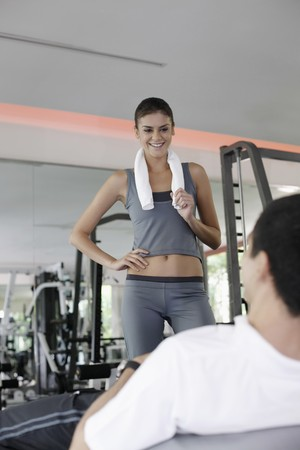 Personal trainer helping man exercising in gymnasium photo