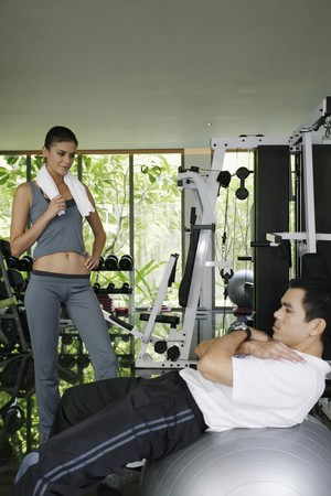 Personal trainer helping man exercising in gymnasium Stock Photo - 7446957