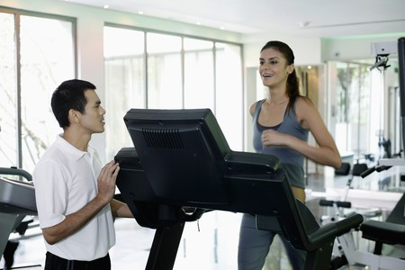 Woman running on treadmill, personal trainer watching photo