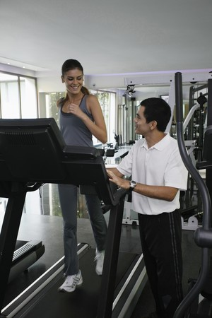 Woman running on treadmill, personal trainer watching Stock Photo - 7446801
