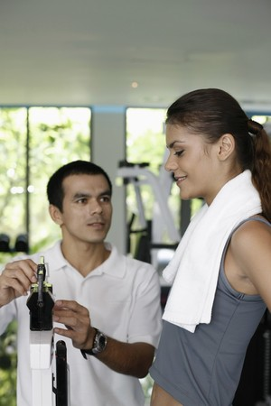 gewicht skala: Frau, stehend auf der Waage, personal-Trainer-pr�fen Ihr Gewicht  Lizenzfreie Bilder