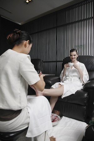 Spa attendant massaging a womans foot photo