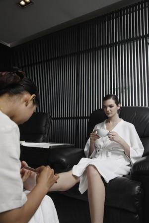 Woman enjoying a cup of tea while getting a pedicure photo