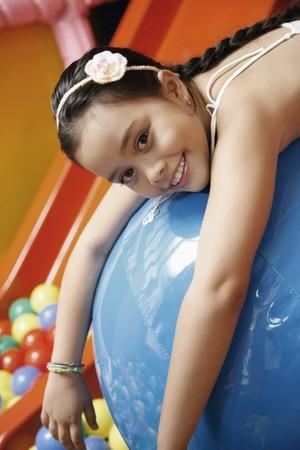Girl lying forward on blue ball photo