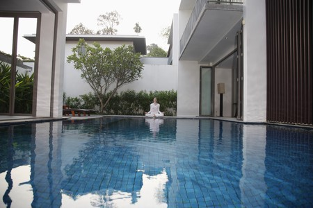 Woman meditating by the pool side photo