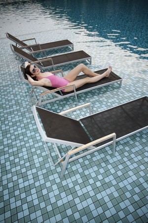 Woman with sunglasses relaxing on lounge chair photo