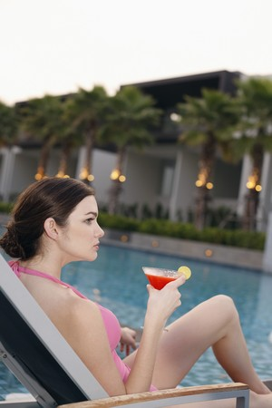 Woman holding a glass of fruit juice while relaxing on lounge chair photo