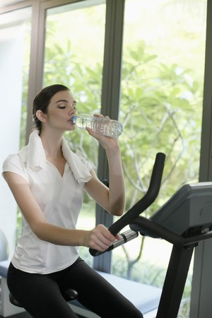 Woman drinking water while exercising in the gymnasium photo