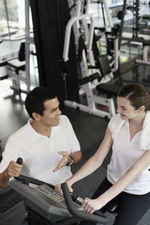 Personal trainer helping woman exercising in gymnasium Stock Photo - 7446357