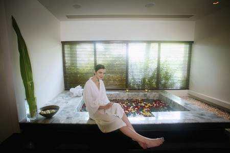 Woman sitting beside bathtub with flower petals photo