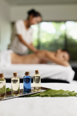 Bottles of massage oil, woman receiving back massage in the background photo