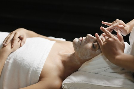 Woman in health spa, having cream applied to face photo