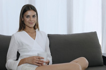 Woman sitting on couch holding a cup Stock Photo - 7446593
