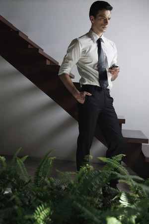 Businessman with mobile phone contemplating photo