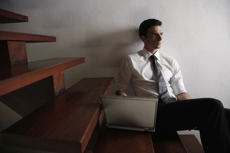 Businessman sitting on stairs using laptop Stock Photo - 7446529