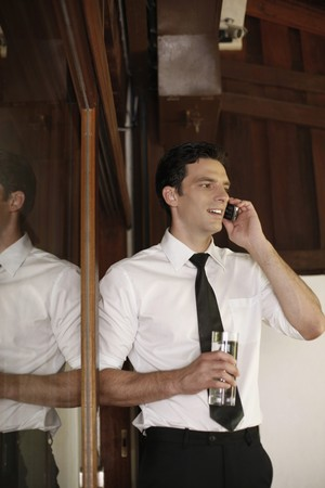 Businessman holding a glass of water while talking on the phone photo