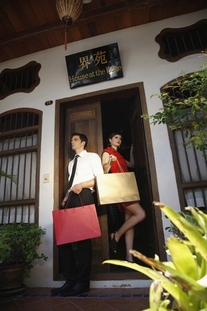 Man and woman with shopping bags standing at the doorway Stock Photo - 7446487