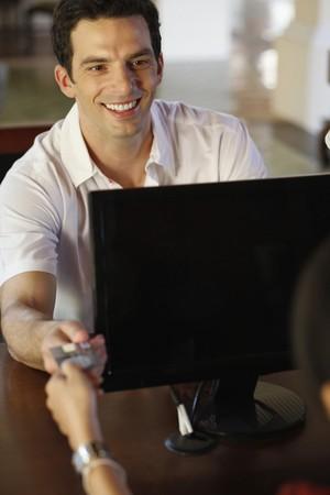 Man giving credit card at hotel reception desk photo