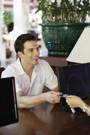 Man giving credit card at hotel reception desk Stock Photo - 7446345