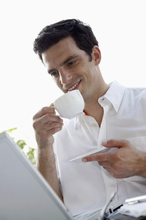 southeastern european descent: Man drinking coffee while using laptop Stock Photo
