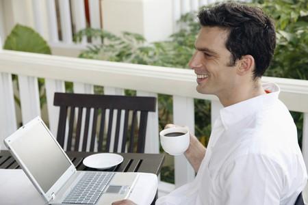 Man drinking coffee while using laptop photo