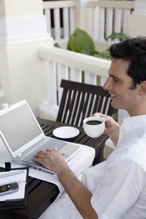 hombre tomando cafe: Hombre bebiendo caf� mientras se utiliza el port�til