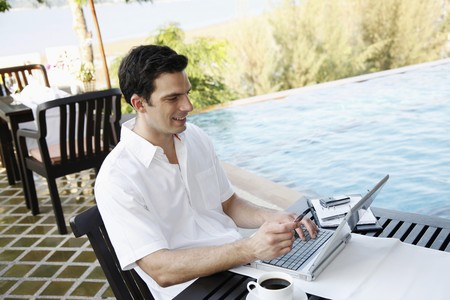 Man holding credit card while using laptop photo
