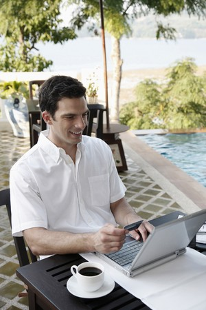 Man holding credit card while using laptop Stock Photo - 7446553